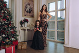 mother and daughter posing with christmas tree