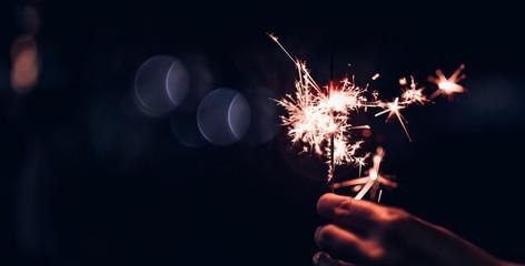 Hand holding burning Sparkler blast on a black bokeh background at night,holiday celebration event party,dark vintage tone.