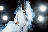 Young fencer athlete wearing fencing costume holding the sword and mask. Isolated on black background with lights