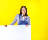 Business Concept. A girl in a dress suit on a yellow studio background holds a large white sheet, a place for an inscription. Copy space.
