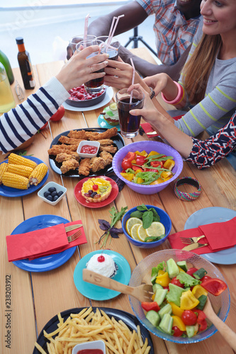 Top view of group of people having dinner together while sitting at wooden table. Food on the table. People eat fast food. - 238203912