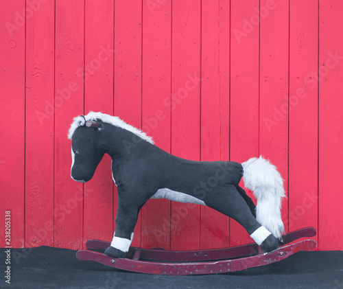 Wooden rocking horse on a red wooden wall
