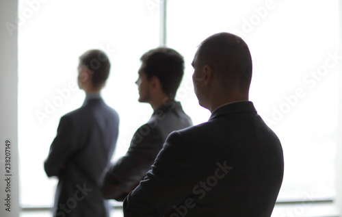 back view three employees as they look out on a large window overlooking the city - 238207149