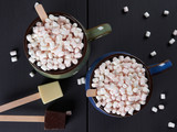 Two cups with hot chocolate and mini marshmallows, one cup being blue and the other one green, with white and dark chocolate cubes, on dark brown background - 238208992
