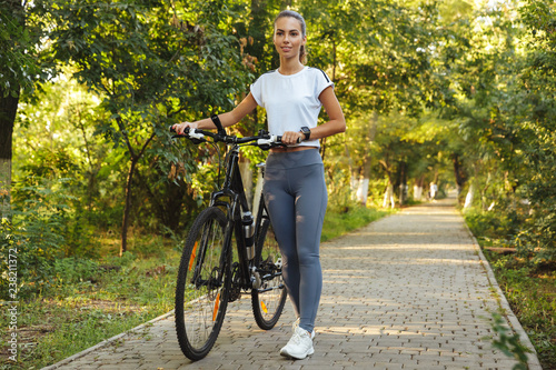 Image of happy woman 20s walking with bicycle through green park, during sunny day - 238211372