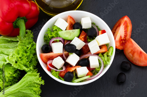 Greek salad with fresh vegetables, feta cheese and black olives on a dark background. Top view