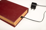 Old book with a battery charging cable - 238218345