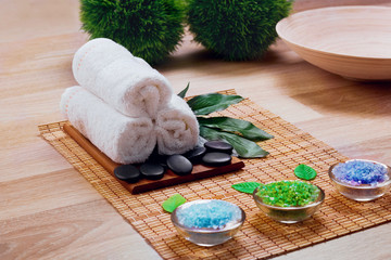 Beautiful spa and wellness setting composition on massage table in relax center on blackboard with copy space.Towel, Salt, Plumeria Flower, Hot stones Bowl for spa therapy.Spa  products © verona_studio