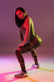 Attractive young brunette woman in the studio dancing Booty dance on a dark background - 238230594