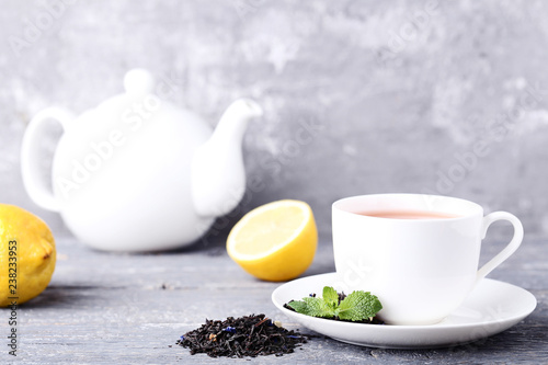 Cup of tea with mint leafs, lemons and teapot on grey wooden table