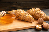 Fresh croissants with honey jar and nuts
