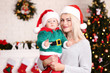Mother and son in santa hats celebrate christmas at home