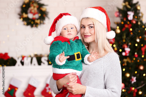 Foto Murales Mother and son in santa hats celebrate christmas at home