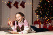 Young girl with notepad and pencil lying near christmas tree at home
