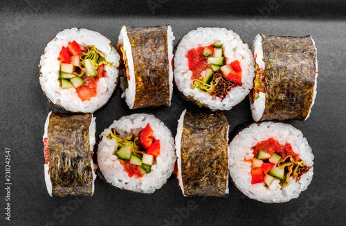 Sushi Roll - Maki Sushi with pepper, cucumber, tomato and cabbage on black plate isolated over white background. Japanese cuisine. Vegan food concept. Top view - 238242547
