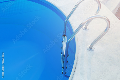 Close-up of a part of swimming pool with a stainless steel ladder and blue water on sunset. Summer vacation, holidays, relax, summer activities concept