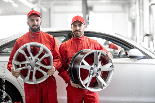 Portrait of a two auto mechanics in red uniform with alloyed wheels at the car service