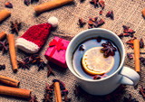 Cup of Christmas tea with gift and ingredients around on jute background