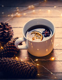 Cup of tea and Christmas box gift with pine cones and Fairy Lights on wooden background - 238271399