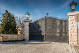 Metal driveway security entrance gates set in brick fence