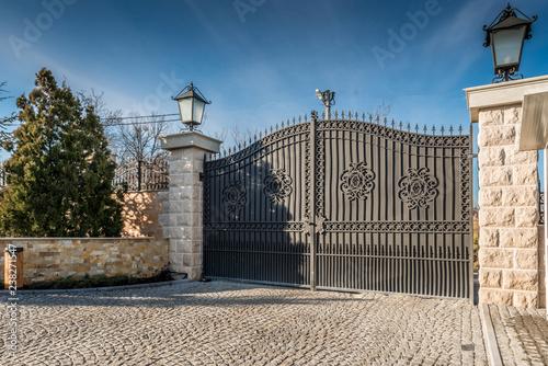 Metal driveway security entrance gates set in brick fence - 238271547