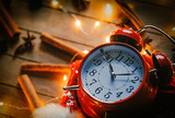Vintage alarm clock and cinnamon, star anise with Christmas lights around on wooden background - 238271986