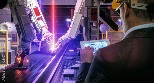Smart automation industry robot in action welding metall while engineer uses his remote control table pc- industry 4.0 concept - 3D rendering - 238274184