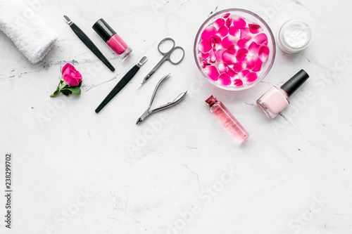 Leinwanddruck Bild manicure equipment with nail polish and rose petals white stone background top view mockup