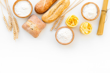 Farinaceous food. Fresh bread and raw pasta near flour in bowl and wheat ears on white background top view copy space