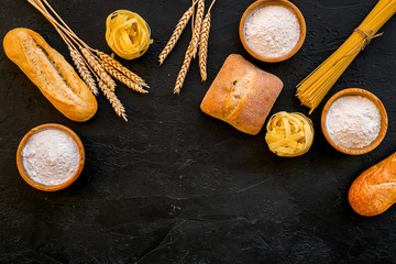 Bakery production, making bread and pasta. Fresh bread and raw pasta near flour in bowl and wheat ears on black background top view copy space