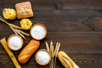 Homemade fresh bread and pasta near flour in bowl and wheat ears on dark wooden background top view copy space