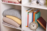 shelves with various things in the room - books, watches, knitted blankets - 238315191