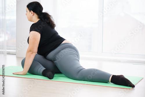 Fototapeta flexibility, grace, good mood, healthy lifestyle,vitality, yoga. pilates fat burning workout for women. overweight lady stretching in yoga studio