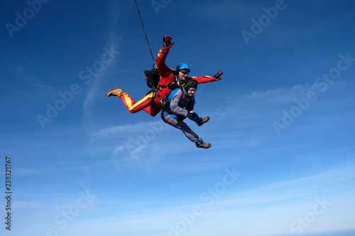 Tandem skydiving. Two happy men are in the sky.