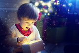 Surprised child opening and looking inside a magic gift over Christmas tree