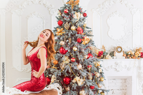 Foto Murales Winter holidays, celebration and people concept - young sexy woman in elegant red dress over christmas interior background