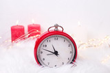 Red clock - symbol of  New Year and birning candles  on white fur background.