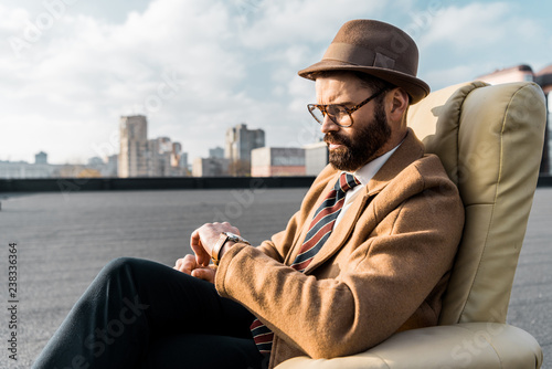 handsome businessman sitting in armchair and looking at watch