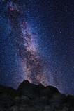 Milky Way and stars in the night sky. Big rocks in the foreground.
