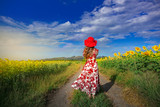 Back view of attractive young woman in hat with long hair in sunflower field enjoying nature,rainbow mountain view.