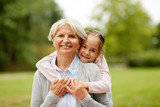 family, leisure and people concept - happy granddaughter hugging her grandmother at summer park - 238351912