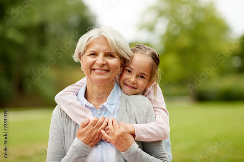 mata magnetyczna family, leisure and people concept - happy granddaughter hugging her grandmother at summer park