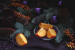 Still life composition with persimmons, sea buck-thorn and fir branches in dark and moody style