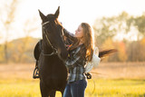 Girl equestrian rider stands near the horse. Horse farm. Horse theme  © Rakursstudio