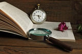Magnifying glass, pocket watch and book