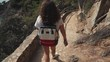 Lovely brunette woman spending day hiking in mountains, viewing nature. Beautiful journey on summer vacation, walking on mountain path.