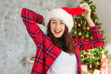 Young beautiful brunette woman in plaid checkered pajamas in decorated bedroom interior with gift box and Chrictmas tree on background. People on Christmas morning concept. Close up, copy space. - 238366174