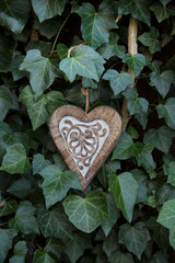 decorative wooden heart hanging on a ivy covered wall