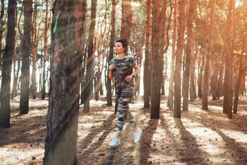 Young fitness woman running at morning. Woman wearing military-colored clothing and smart watch
