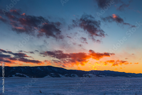 the sun sets behind the mountains and colors the clouds in winter, Altai, Russia - 238378985